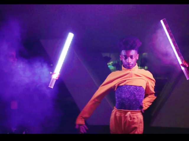 a vogueing scene with smoke and colored lights outside with a fierce individual